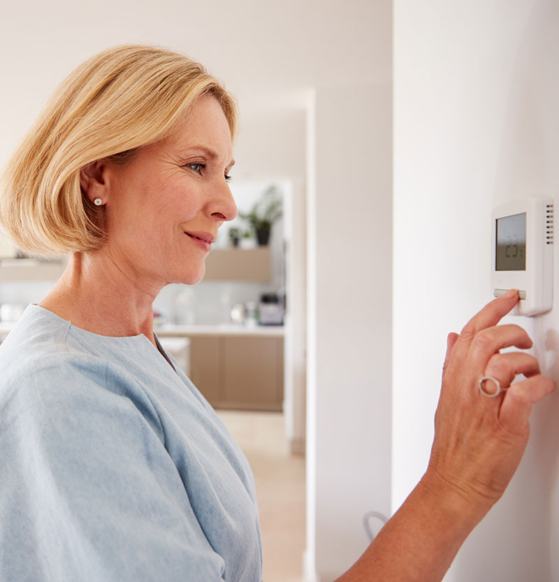 close-up-of-mature-woman-adjusting-central-heating-BYMNWEP