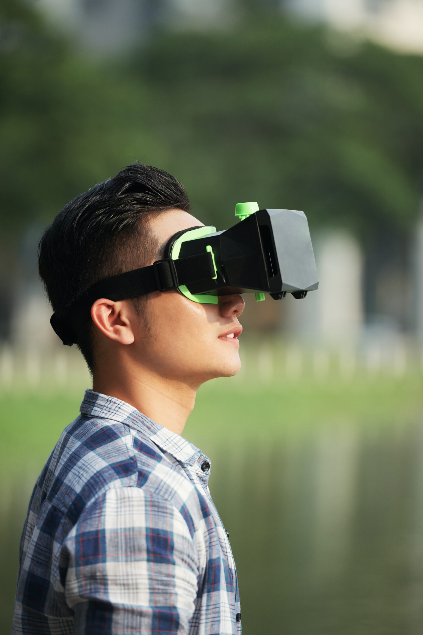 Young Vietnamese man in vr goggles standing in the street