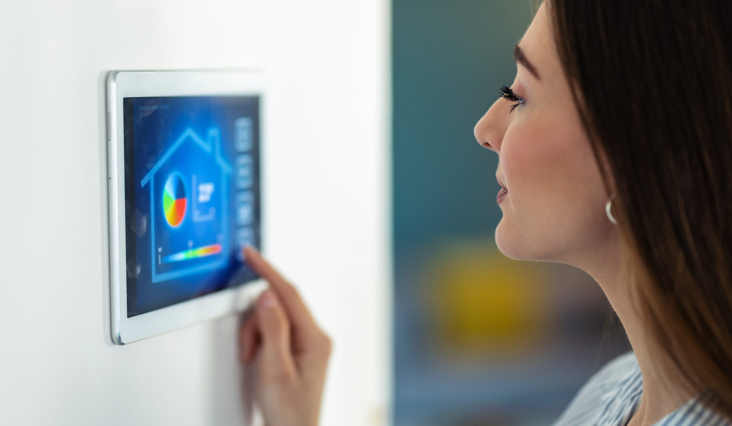 Shot of pretty young woman using the home automation system on digital tablet to regulate the temperature.