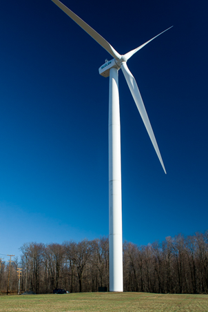 A wind turbines in the Forward Wind project in Somerset County, PA, dwarfs a utility pole and a nearby forest.