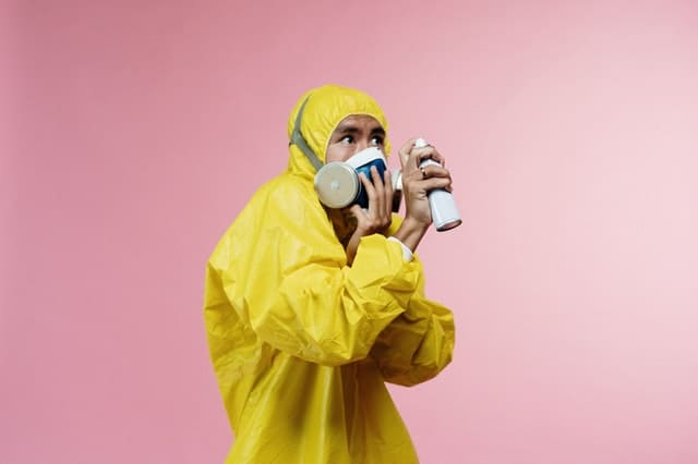A man in a yellow protective suit with a mask fearfully spraying a sanitizer.