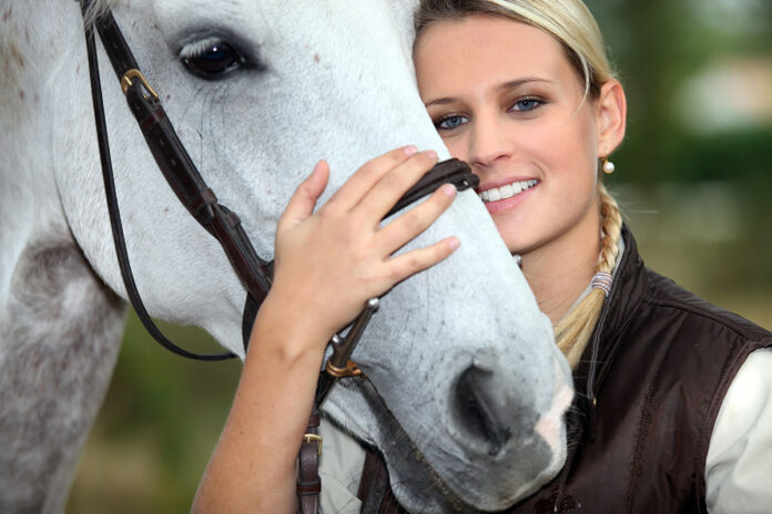 Woman gives horse an equestrian subscription box