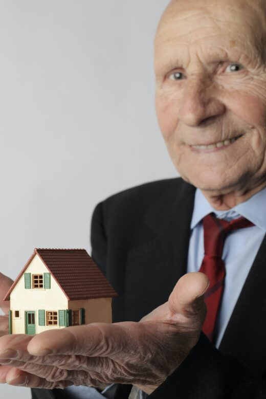 Photo: Older man holding a home in his hands