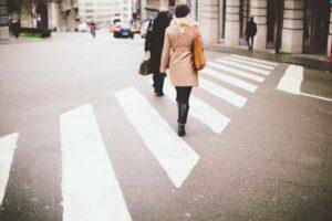 A woman crossing the street a crosswalk