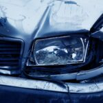 An Audi with front end damage to the grill and headlight