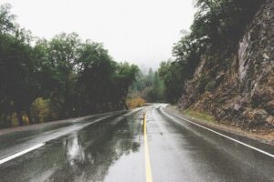 A wet two lane road on an overcast day