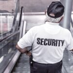 A security guard riding down an escalator