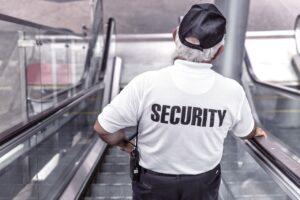 A security guard riding down an escalator