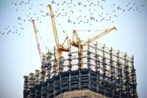cranes atop a skyscraper under construction