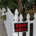 fence with a beware of dog sign