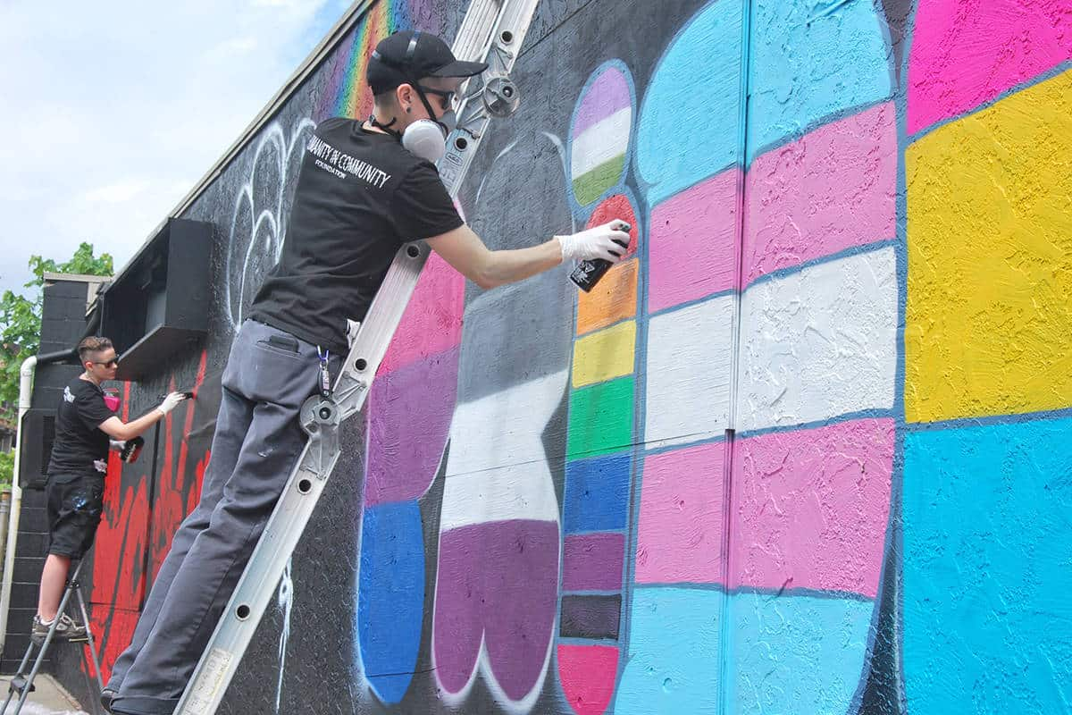 Humanity In Art painting a pride themed mural