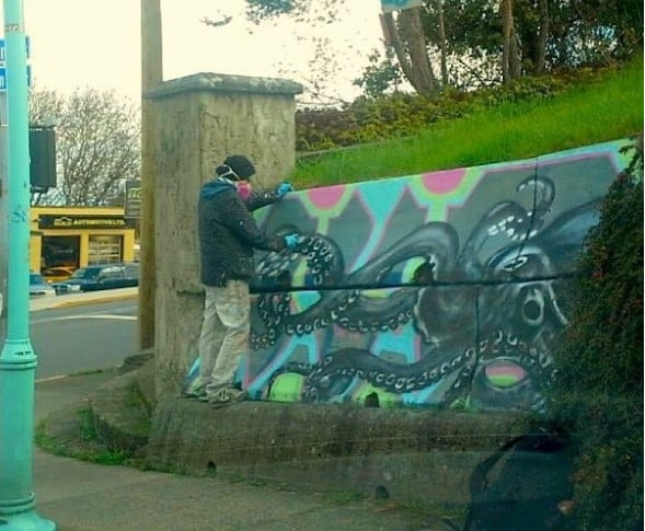 Person standing on concrete block painting a black octopus.