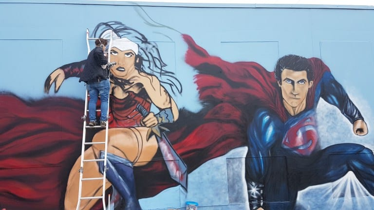 Lys Glassford on a ladder painting a wonder woman mural