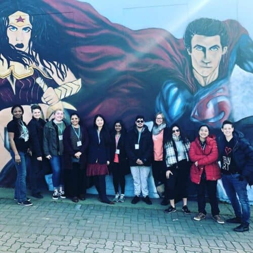 Group poses infront of mural of Wonder Woman and Superman