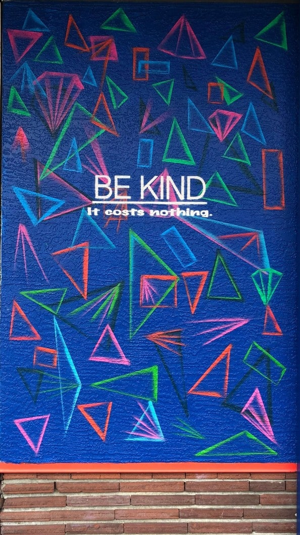 Abstract mural with the words ' Be Kind, It Costs Nothing'.