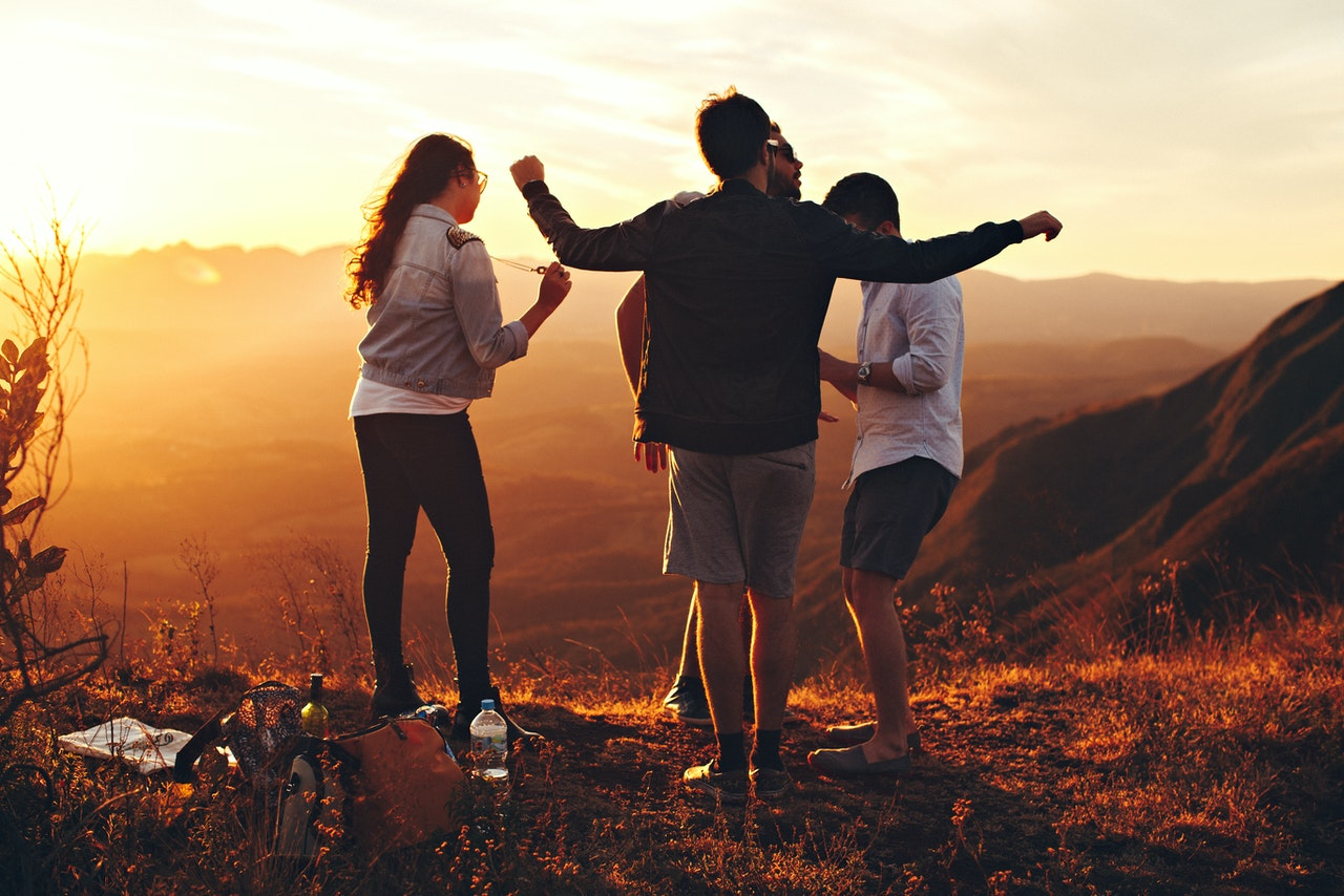 four-person-standing-at-top-of-grassy-mountain-697244 (1)