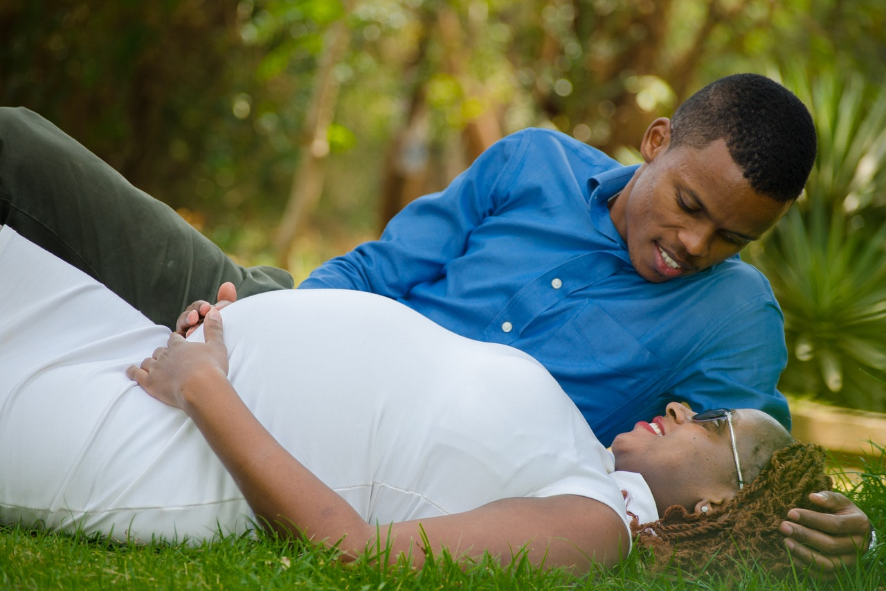 pregnant-woman-lying-beside-man-in-grass-ground-2146911
