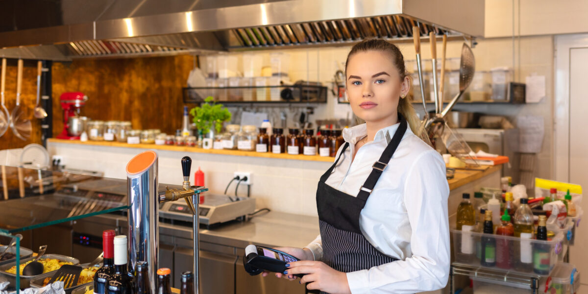 Waitress,Standing,At,Cash,Counter,Holding,An,Electronic,Card,Payment