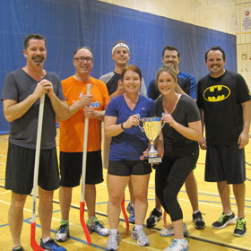 A group of employees playing floor hockey