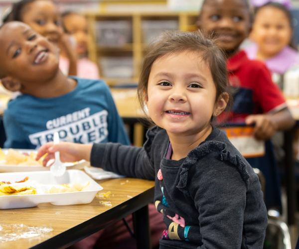 Photo: Student at table smiling at the camera