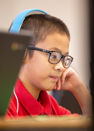 Photo: Student with headphones looking at computer