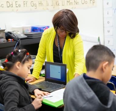 Photo: Teacher helping student on computer