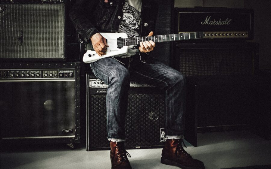 guitar player sitting on an amp