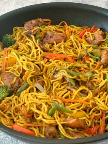 Guyanese chicken chowmein with carrots and vegetables in a black wok