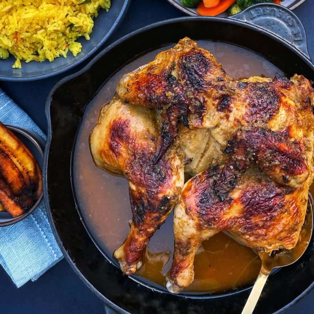 Roasted spatchcocked chicken in a skillet, with peeks of sides