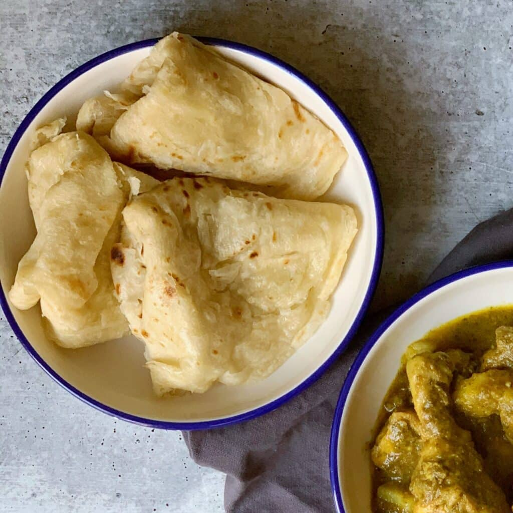 Three Guyanese oil roti in a white, blue rimmed bowl on a gray napkin with another white blue rimmed bowl with Guyanese chicken curry