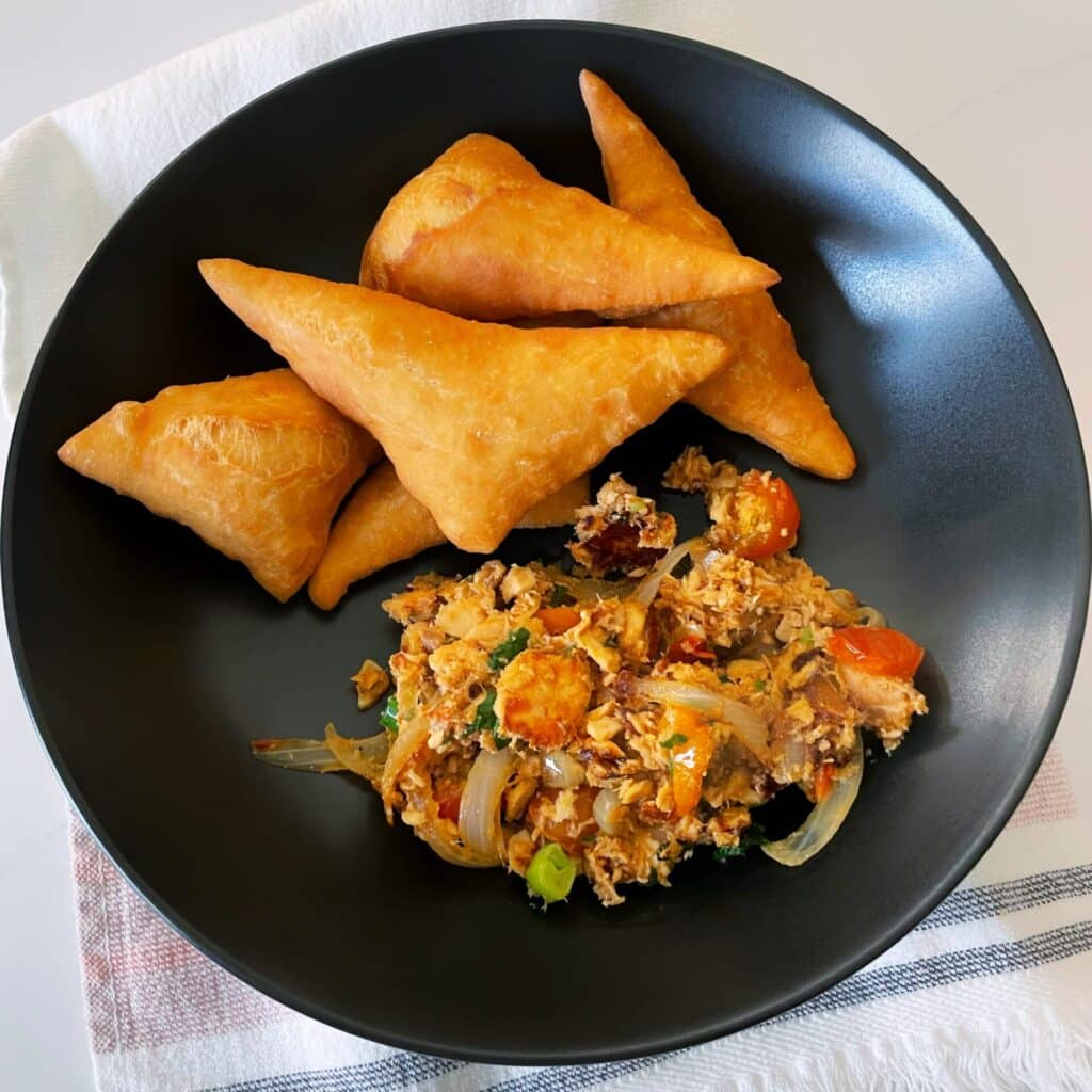 Triangle shaped Guyanese Style Bakes with sautèed can salmon on a black plate resting on a white towel with pink and gray stripes