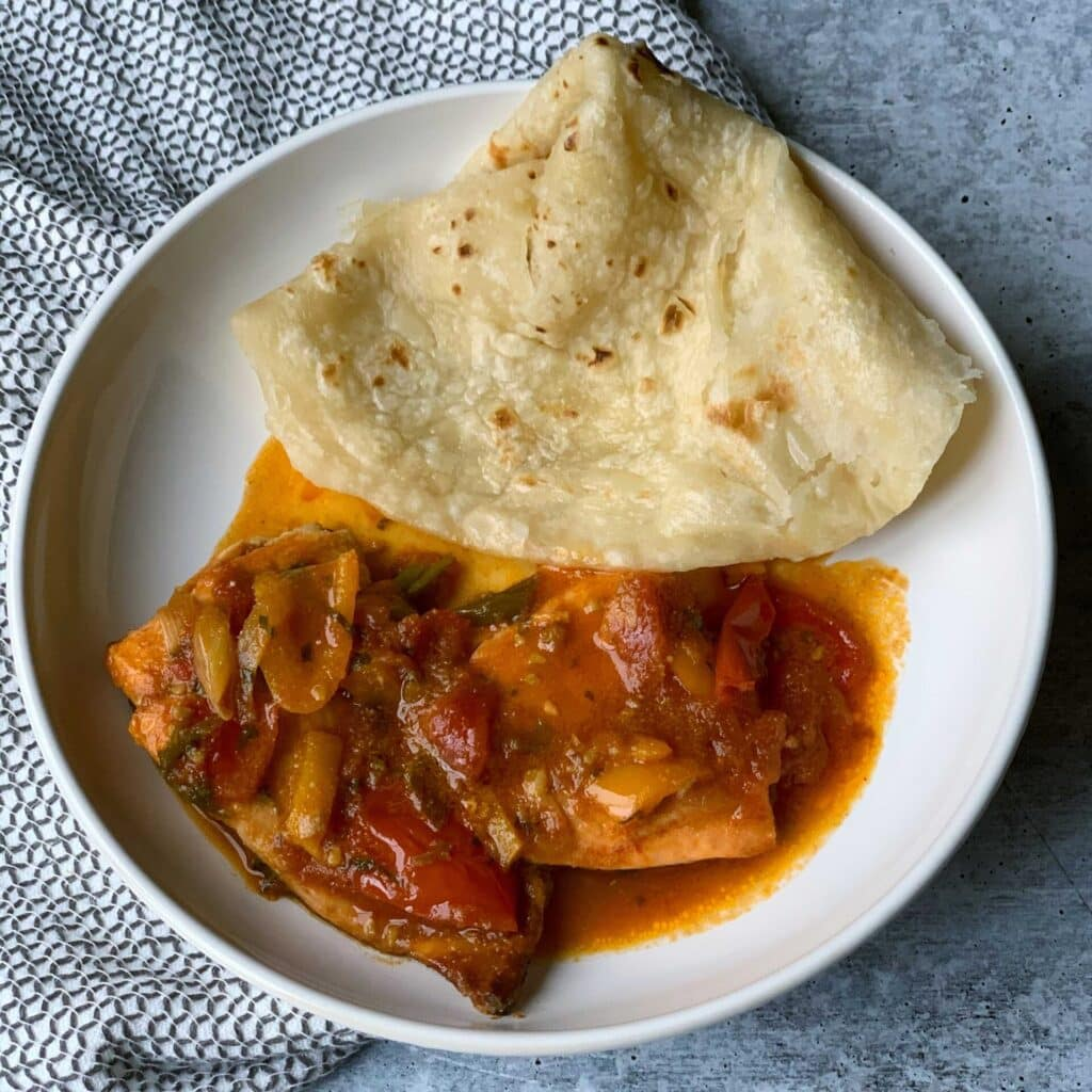 Guyanese Oil roti in a white bowl with red Caribbean stew fish. The plate is on a white towel with grey circles