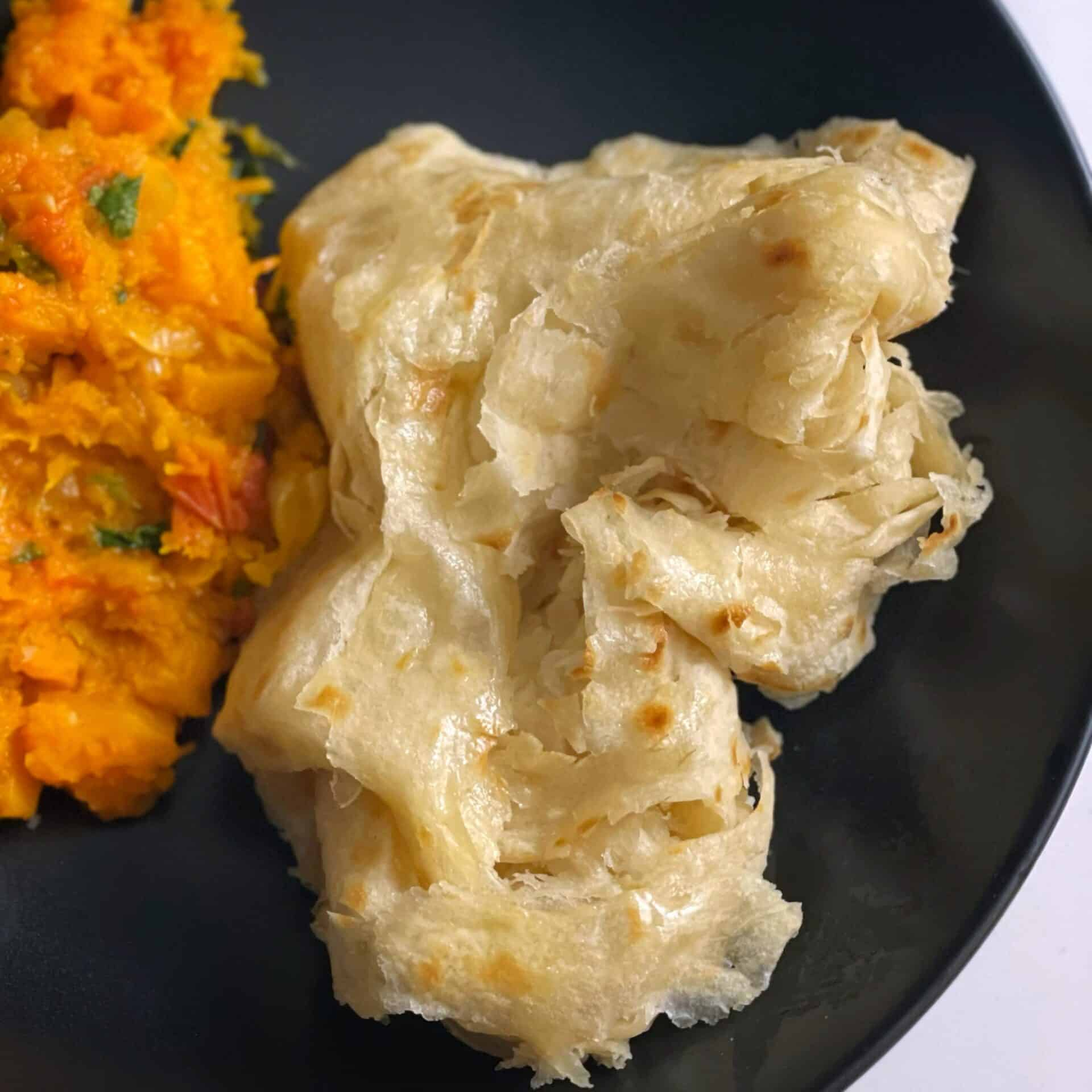 Guyanese oil roti in a black plate, with a side of pumpkin