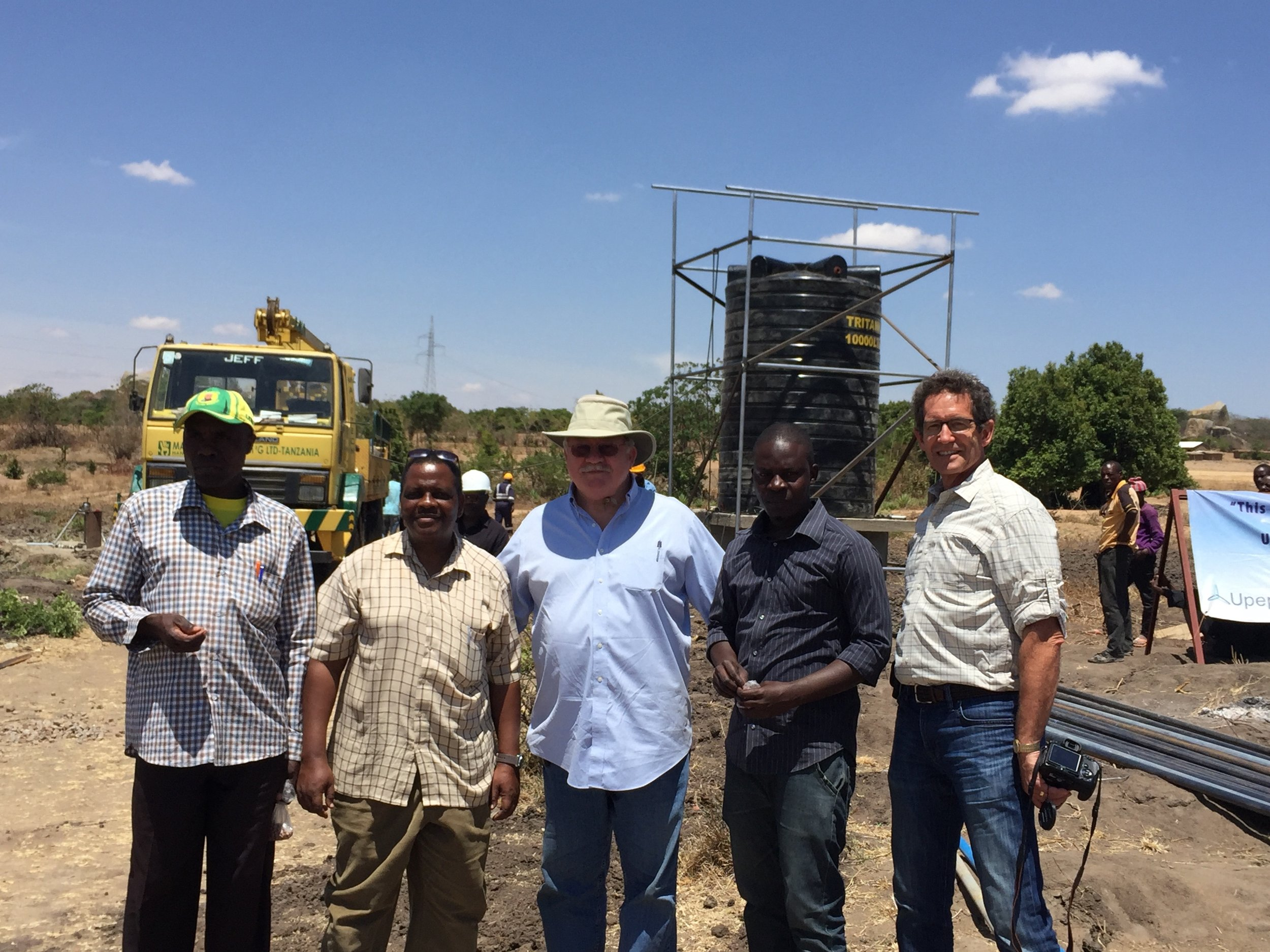 Upepo team stands in front of a well under construction in the Msikii Village