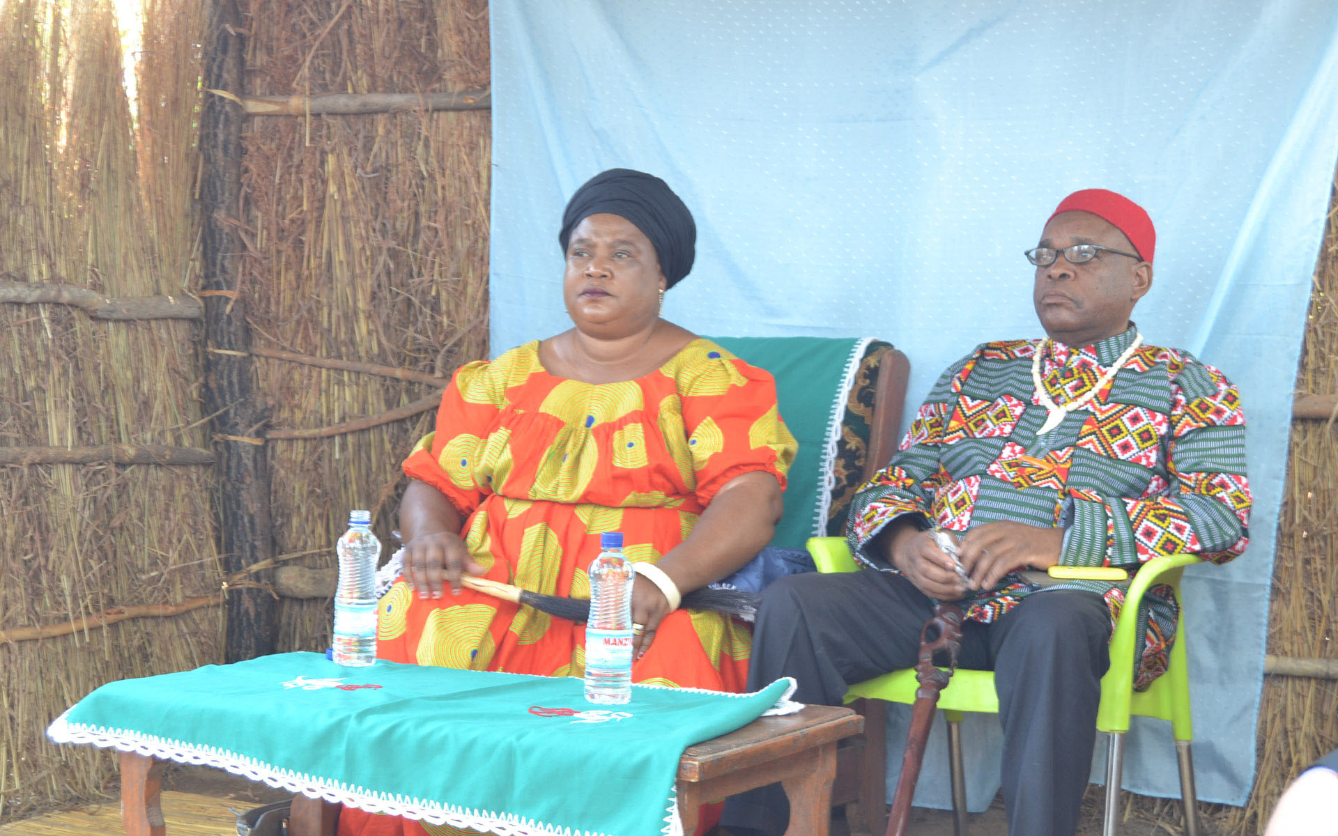 Chieftainess Malembeka, the traditional ruler and landowner, presides over a village meeting, accompanied by her husband.