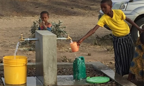 Two children stand at a well filling buckets with water at the Singida Solar Project site.