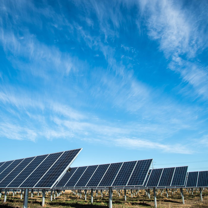 Field of solar panels with a blue sky