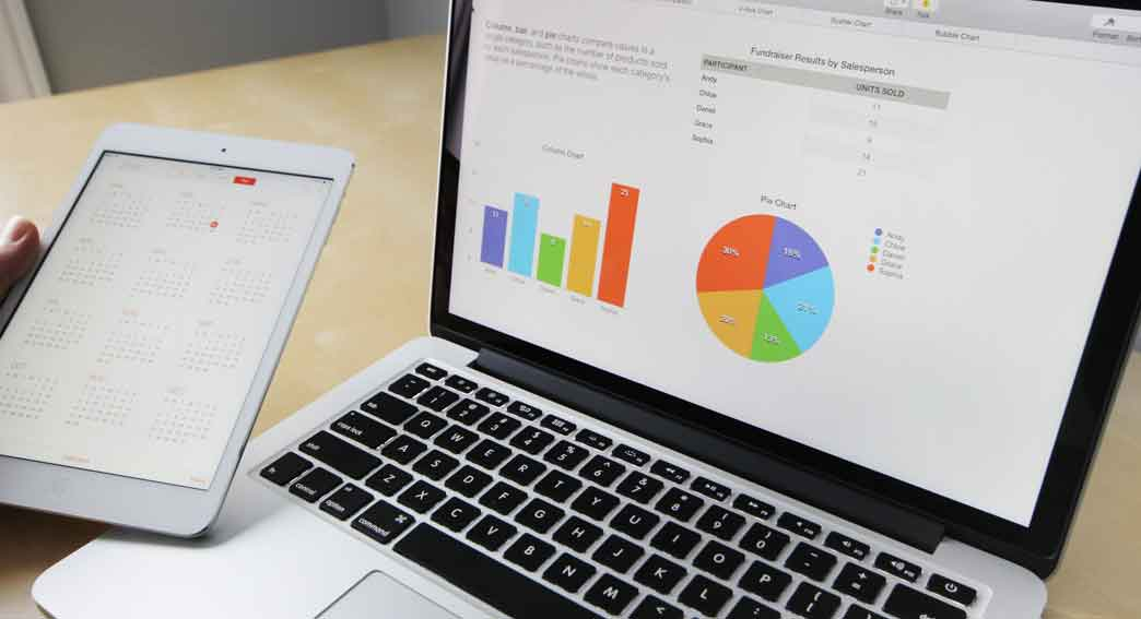 A laptop with financial graphics and a tablet for QuickBooks® and other Accounting Software