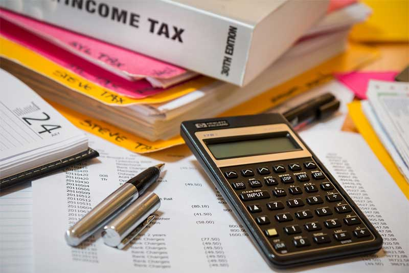 Pile of tax materials with an income tax book, papers and a calculator