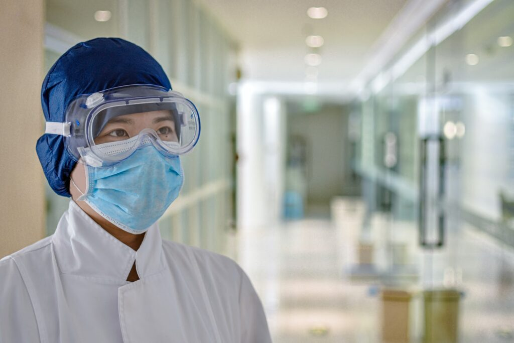 woman in goggles and mask in hospital coronavirus waste management