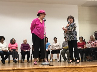 Older adults stand onstage presenting with a microphone. Others sit behind them looking on.