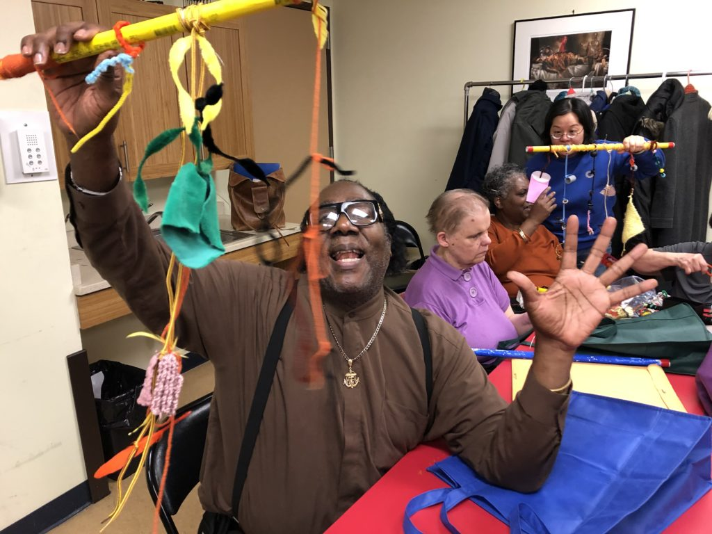 An older adult plays with a coloful stick that has multiple threads and strings and yarns hanging from it. They are excited and full of energy.