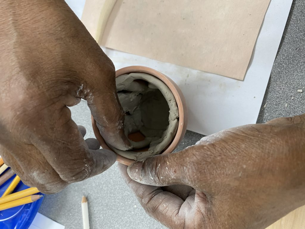 Overhead shot of an older adult moulding clay into a terracotta planter. Their hands are marked with messy clay.