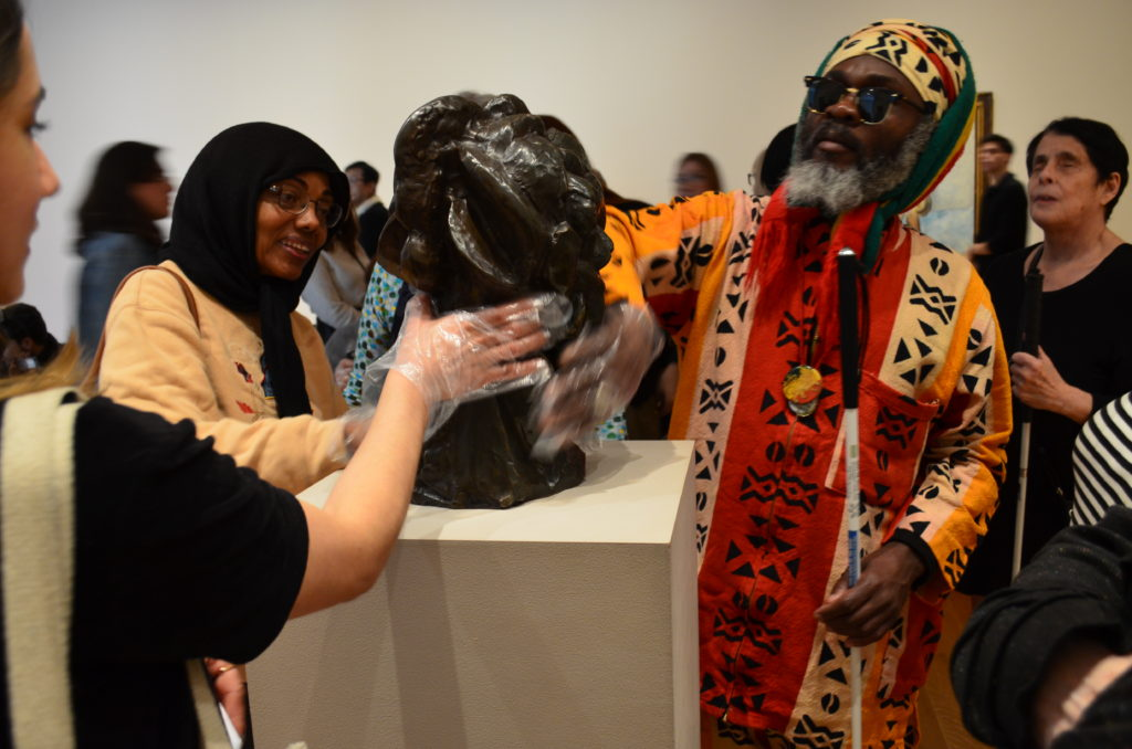 Older adults with gloved hands are touching a piece of artwork on a communal table. The group is dressed colourfully, and one participant wears a headscarf.