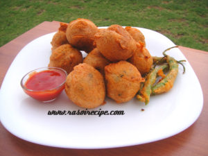 Aloo vada served with green chillies and ketchup.