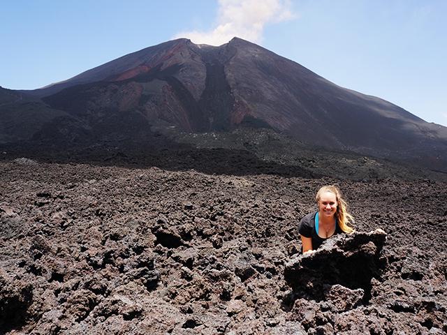 peeking behind rocks at pacaya volcano