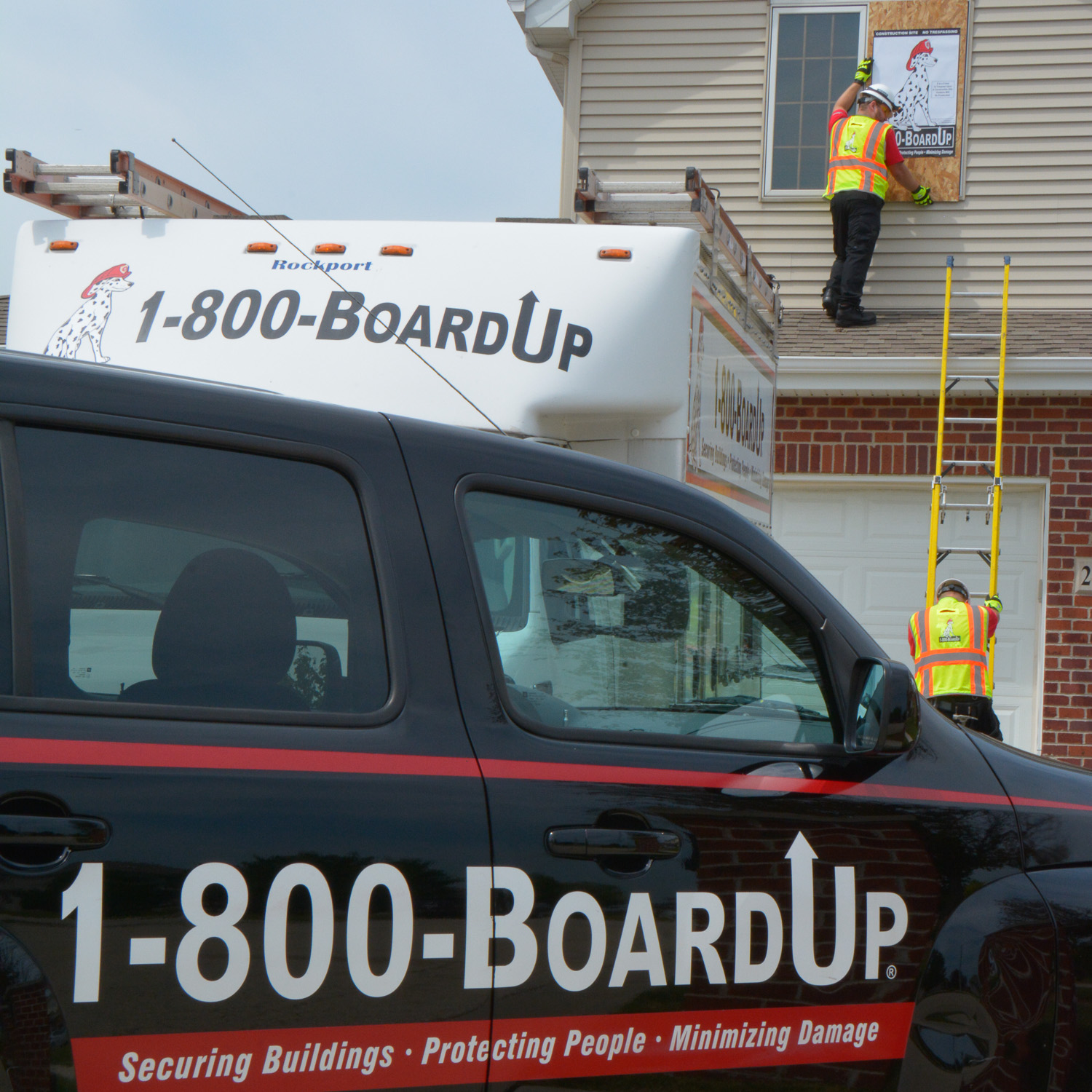 boardup vehicle in front of house. crew climbing ladder onto roof