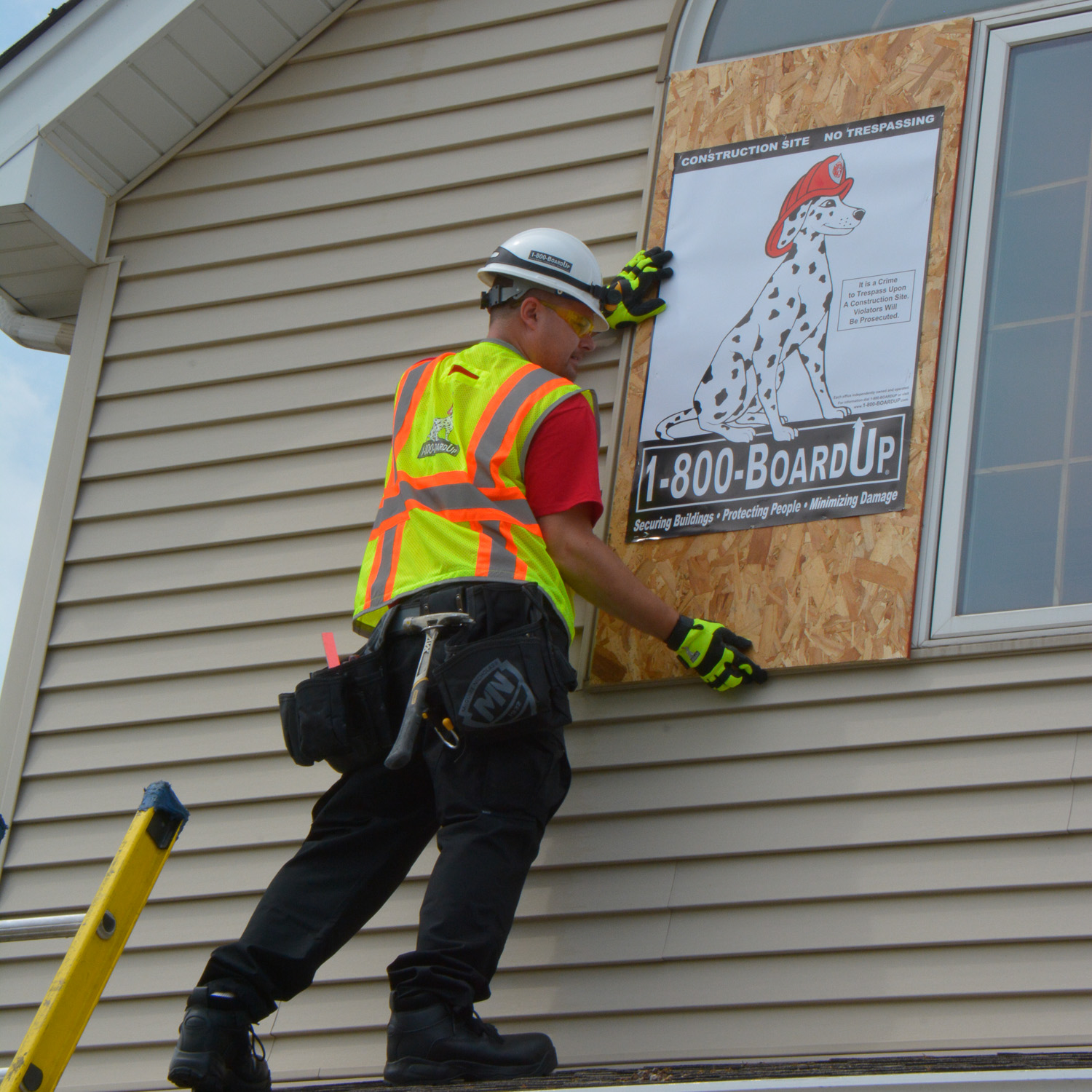 boardup crew member boarding up a window on a house