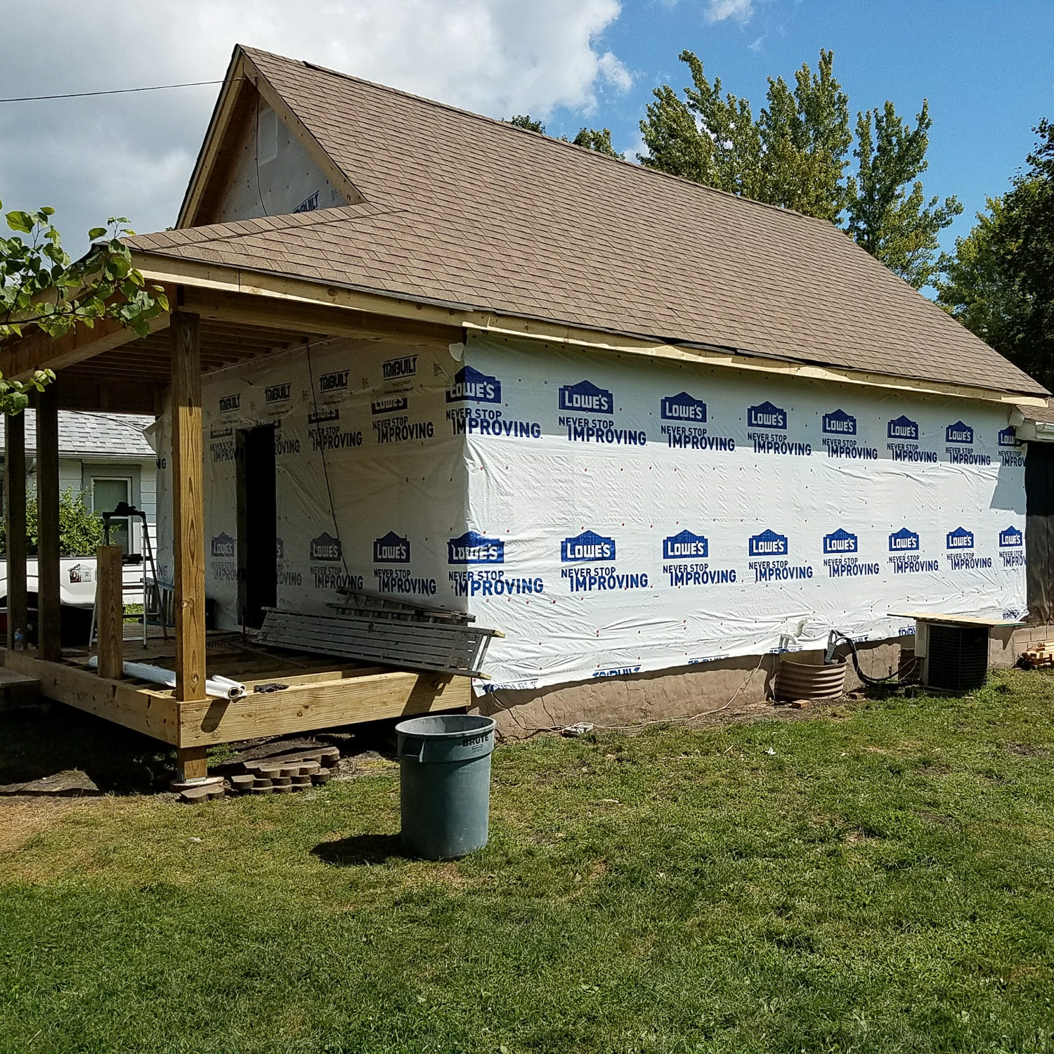 house during wind damage restoration process. House framed, new roof installed, no siding yet, during construction.