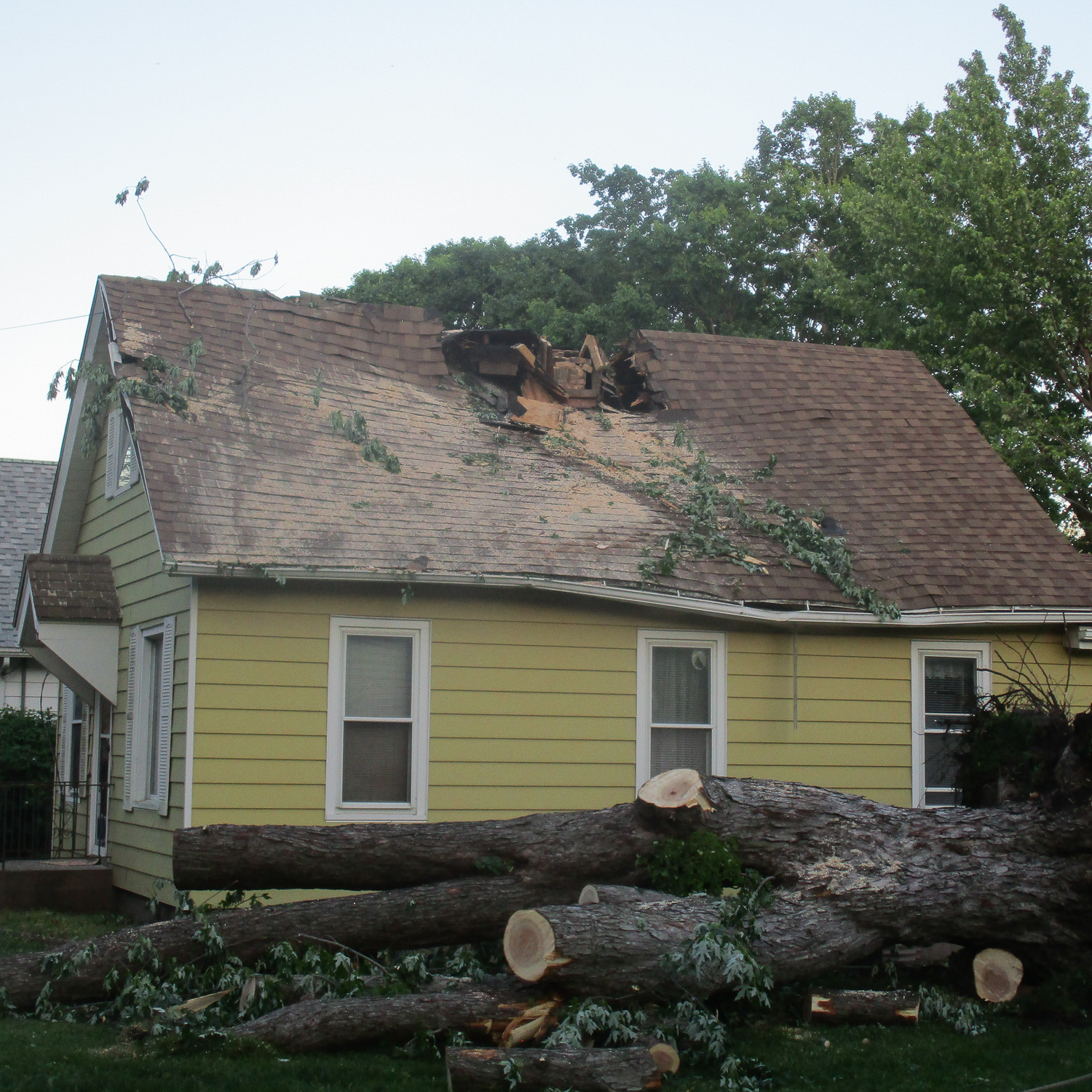roof damage from fallen tree-large hole in roof from tree impact.